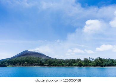 """Anak Rakata, """"Child of Krakatau"""" smokes gently on a clear day. It is not erupting, but bare lava flows attest to recent activity."""