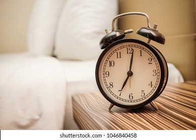 Analog alarm clock is on bed side table, time 7 o'clock in the morning. Time to wake up.