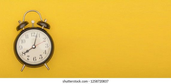 Analog alarm clock on yellow color background, timing theme