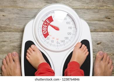 Analog bathroom scale indicating child obesity