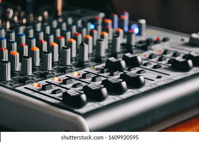 An analog Behringer Mixer with faders set and  lights onmixer