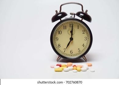 Analog clock with medicine isolated on white background.