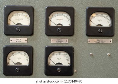 Analog dials on wall panels showing current and volts.