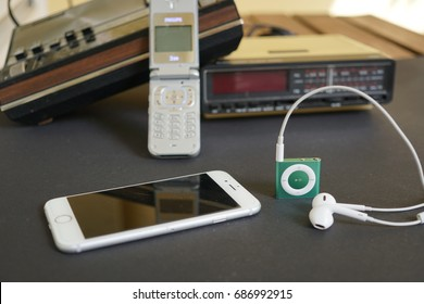 Analog to digital: old radios, cell phone, iPhone and iPod with earphones