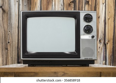 Analog television on table with rustic wod wall.