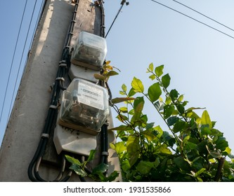 Analog watt hour electric meter on power pole with beautiful green leaves and blue sky background.