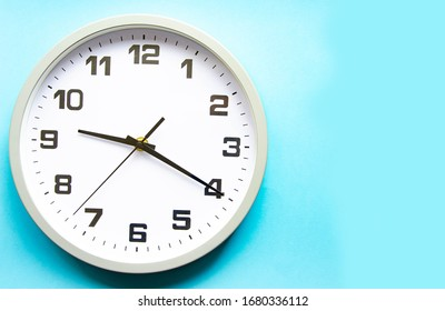 Analog white clock on a blue background. Clock in closeup. Place for text. Business, are you ready.