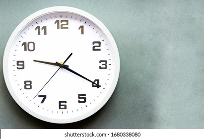 Analog white clock on a gray background. Clock in close up. Place for text. Business, are you ready.
