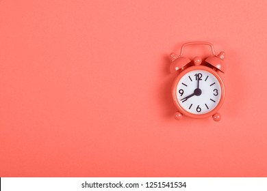 Analogue alarm clock on coral background. Living Coral color of the year 2019.