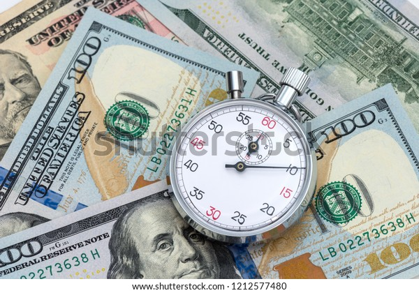 Analogue metal stopwatch on the American dollars banknotes.