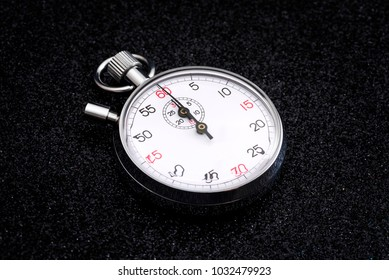 Analogue metal stopwatch on the black background.