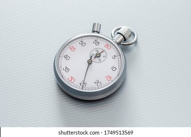 Analogue metal stopwatch on the line metallic background.