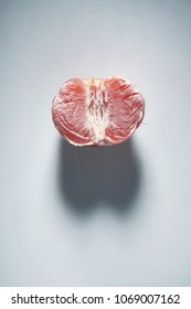 Analogy, a sexual grapefruit in the form of a female vagina, with a shadow in the form of male eggs on a gray background