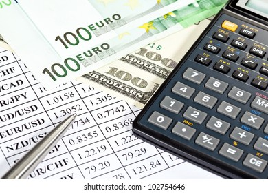 Analysis of financial risks: money, calculator and a pen lying on a currency cross-rate table