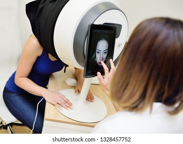 Analysis of the skin. The doctor Cosmetologist analyzes the skin of the face of a young pretty woman