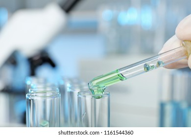 Analyst dripping reagent into test tube with sample at laboratory, closeup. Chemical analysis