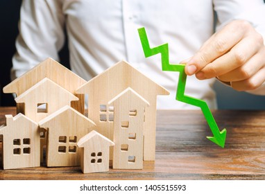 Analyst holds down arrow near the wooden houses. Concept of falling real estate market. Low prices and cost of housing. Reduced mortgage rates and housing demand. Bankruptcy. Crisis and low liquidity
