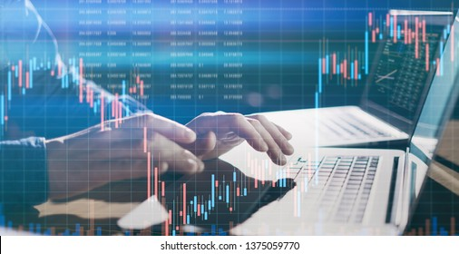 Analyst using laptop and researching the financial data at his office. Concept of a digital diagram, graph interface, virtual screen, technical price indicator, trading online, global market