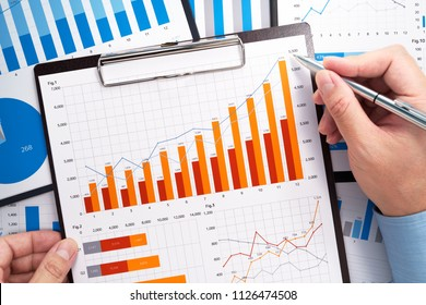 Analyzing business data. Businessman gathering statistical data. Growth charts and graphs. Pile of reports.