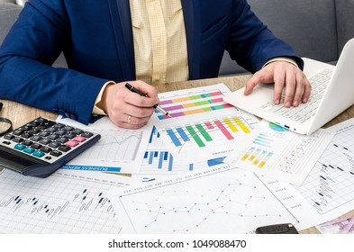 Analyzing business graphs in office by businessman