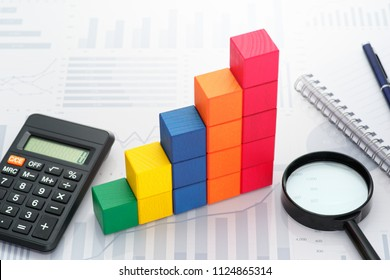Analyzing data. Gathering statistics. Business data processing. Toy block steps, calculator and magnifier on many charts background.