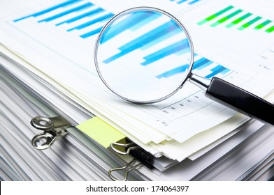 Analyzing the data. Scanning business documents. Magnifying glass on the stack of documents.