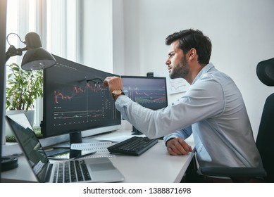 Analyzing data. Thoughtful young trader is pointing at graphs on computer screen while working in his modern office.