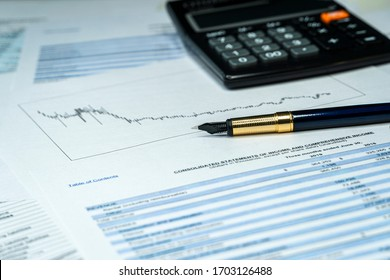 Analyzing finance report with calculator and pen. Investment report in crisis time