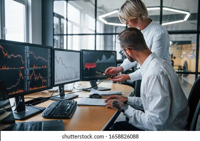 Analyzing information together. Two stockbrokers in formal clothes works in the office with financial market.