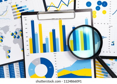 Analyzing marketing reports. Gathering statistical data. Pile of reports. Many charts and magnifying glass.