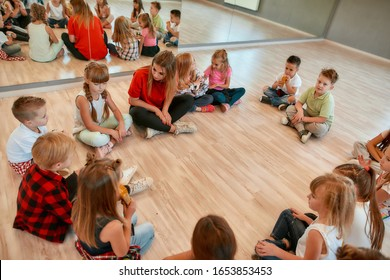 Analyzing mistakes. A group of little dancers sitting on the floor gathered around their female dance teacher and listening her carefully. Dance school. Relationship between teacher and kids