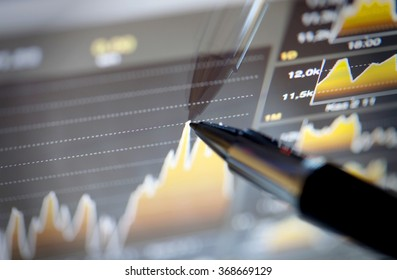 Analyzing stock market from computer screen with a detailed diagram.