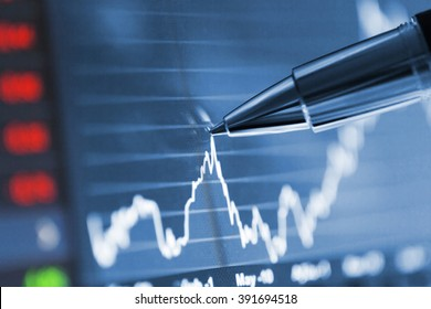 Analyzing stock market from a digital computer screen over a detailed diagram. Pointing out some details with a pen.