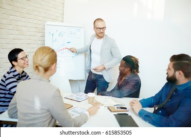 Analyzing work results: confident businessman standing at dry-erase board and drawing productivity graph while his colleagues sitting in boardroom and listening to him attentively
