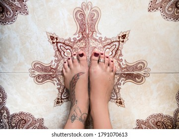 ANANTAPUR, ANDHRA PRADESH / INDIA - NOVEMBER 27, 2018: Feet with a tattoo and rings on the floor