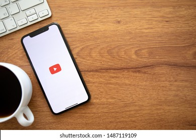 Anapa, Russia - August 1, 2019: iPhone X with multinational entertainment company Google provides streaming media and video YouTube on the screen and background wooden desk.