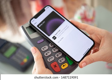Anapa, Russia - August 10, 2019: Woman hand holding iPhone X with Apple Pay Cash on the screen and pay pass online terminal. iPhone was created and developed by the Apple inc.