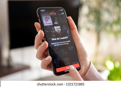 Anapa, Russia - February 20, 2019: Woman holding iPhone X with multinational entertainment company Netflix provides streaming media and video on the screen.