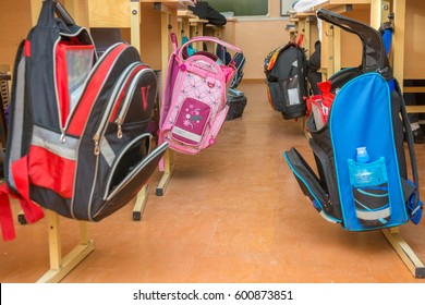 Anapa, Russia - February 28, 2017: School bags hanging on hangers on both sides of the aisle between the desks in the classroom