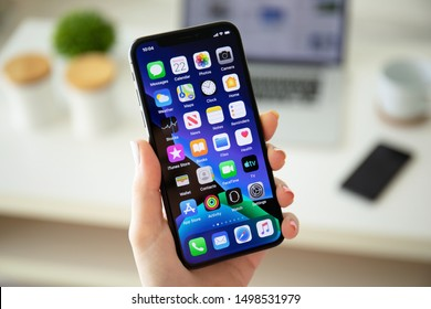 Anapa, Russia - July 22, 2019: Woman hand holding iPhone X with home screen IOS 13. iPhone was created and developed by the Apple inc.