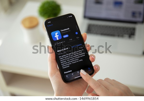 Anapa, Russia - July 22, 2019: Woman holding iPhone X with social networking service Facebook on the screen. iPhone was created and developed by the Apple inc.