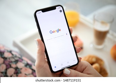 Anapa, Russia - July 25, 2019: Woman holding iPhone X with social networking service Google on the screen. iPhone was created and developed by the Apple inc.