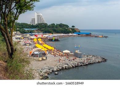 Anapa, Russia - July 26, 2017: Malaya Bay in Anapa resort. People rest on stony beach of Black Sea on Malaya Bukhta sanatorium background. Anapa is popular travel destination for holiday and vacation