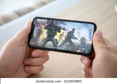Anapa, Russia - October 2, 2019: Man hand holding iPhone 11 with game Call of Duty Mobile in the screen. Games Call of Duty was created by the Activision Publishing, inc.