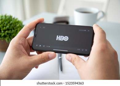 Anapa, Russia - October 3, 2019: Man hand holding Apple iPhone 11 with multinational entertainment company HBO provides streaming media and video on the screen.