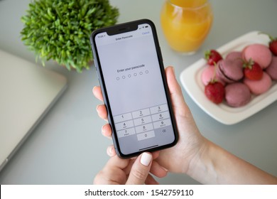 Anapa, Russia - October 3, 2019: Woman hand holding iPhone 11 with Pin code on the screen. iPhone 11 was created and developed by the Apple inc.