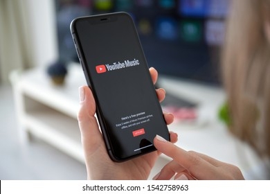 Anapa, Russia - October 4, 2019: Woman holding iPhone 11 with service YouTube Music Premium on the screen. iPhone 11 was created and developed by the Apple inc.