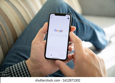 Anapa, Russia - October 9, 2018: Man holding iPhone X with social networking service Google on the screen. iPhone ten was created and developed by the Apple inc.