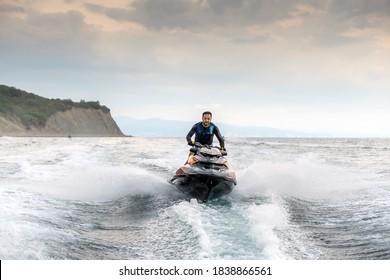 Anapa, Russia - September 5, 2020: Jet ski watercraft driver driving waterbike in Black Sea on seacoast background making splashes
