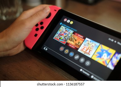 Anapa, Russian Federation - 17 July 2018,  Nintendo Switch, video game console for home or portable gaming. Teenager girl playing game on console. Female hands with handheld Nintendo Switch. Close up